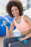 Smiling young woman exercising with dumbbells in gym