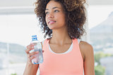 Fit female holding water bottle at gym