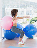 Sporty woman with exercise ball in fitness studio
