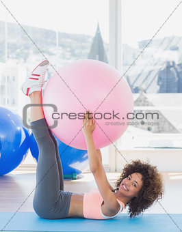 Sporty young woman with exercise ball in fitness studio