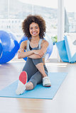 Fit woman sitting on exercise mat in fitness studio