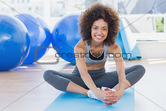 Fit woman doing the butterfly stretch in exercise room