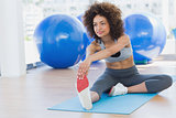 Sporty woman stretching hands to leg in fitness studio