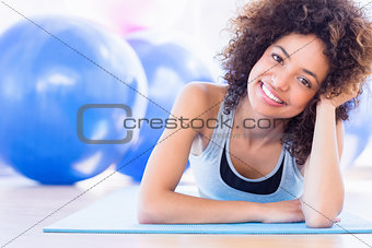 Fit woman lying on exercise mat in fitness studio