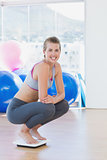 Fit young woman crouching on scale in exercise room