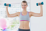 Smiling woman exercising with dumbbells in fitness studio
