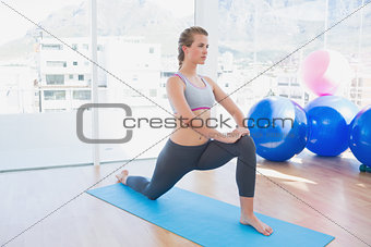 Fit woman stretching leg in fitness studio