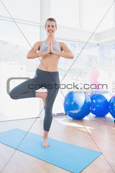 Fit smiling woman standing in tree pose