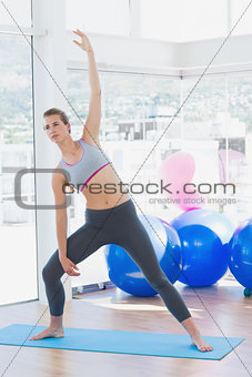 Fit woman stretching hand in fitness studio