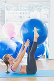 Sporty woman holding exercise ball between legs in fitness studio