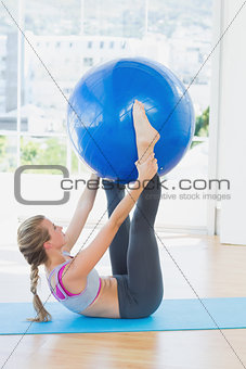 Sporty woman holding exercise ball between ankles in fitness studio