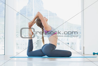Fit woman stretching body in exercise room