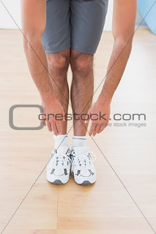 Man touching hands to feet in fitness studio