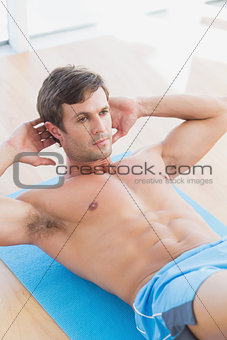 Determined shirtless young man doing sit ups