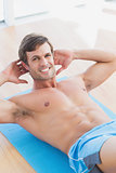 Smiling shirtless man doing sit ups in fitness studio
