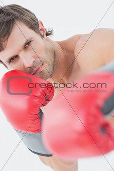 Portrait of a serious young man in red boxing gloves
