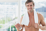 Smiling shirtless man holding water bottle in fitness studio