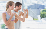 Serious couple standing in boxing stance in fitness studio