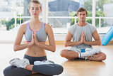 Couple in meditation pose at fitness studio