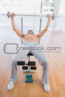 Fit man lifting barbell bench press in gym