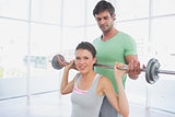 Instructor helping woman to lift barbell in gym
