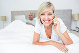 Happy woman using cellphone while man using laptop in bed