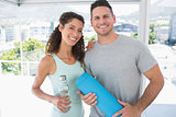 Couple holding water bottle and exercise mat