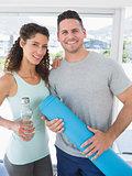 Happy couple holding water bottle and exercise mat