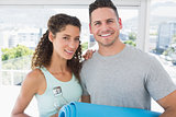 Couple holding water bottle and exercise mat at gym
