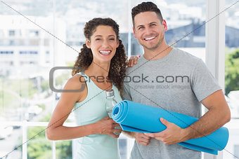 Happy couple holding water bottle and exercise mat at gym