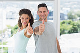 Couple gesturing thumbs up in exercise room