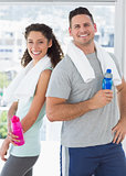 Couple holding water bottles at gym