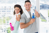 Couple with water bottles gesturing thumbs up at gym