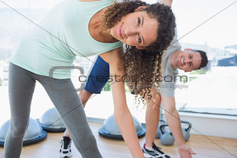 Woman with man doing stretching exercise