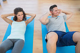 Couple doing sit ups at gym