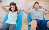 Smiling couple doing sit ups