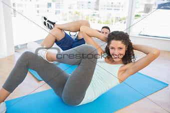 Couple doing sit ups in fitness studio