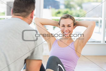 Trainer helping woman doing sit ups