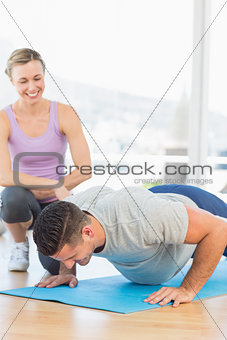 Smiling trainer assisting man with push ups