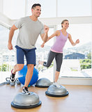 Couple doing step aerobics in fitness studio