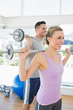 Fit woman and man lifting weights
