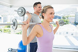 Fit woman and man lifting barbells