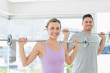 Woman and man lifting barbells at fitness studio