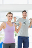 Fit woman and man lifting weights at gym