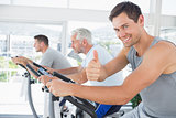 Man on exercise bike gesturing thumbs up