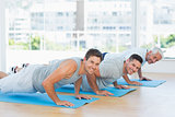 Men doing push ups on exercise mats