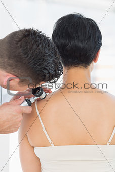 Dermatologist examining mole on woman