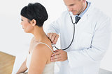 Doctor using stethoscope on back of patient