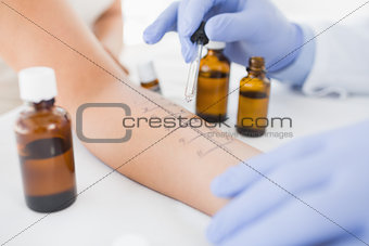 Physiotherapist dropping medicine on hand of patient