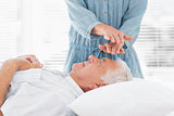 Massage therapist performing Reiki over man